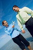 Mid adult couple standing on the beach with a starfish