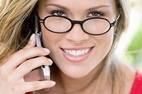 Portrait of a young woman talking on a mobile phone and smiling