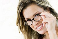 Portrait of a young woman peeking over her eyeglasses