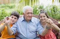 Portrait of a senior man holding his grandchildren's hands and smiling