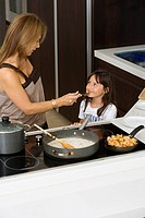 Mature woman feeding her daughter in a kitchen