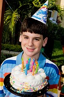 Portrait of a boy holding a birthday cake and smiling (thumbnail)