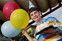 Portrait of a boy holding a birthday cake and balloons (thumbnail)