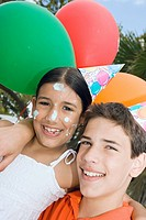 Portrait of a boy with his sister wearing birthday hats and smiling (thumbnail)