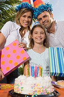 Portrait of a girl smiling with her parents holding birthday presents