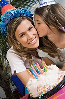 Portrait of a girl kissing her sister in front of a birthday cake