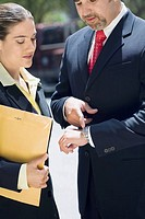 Businessman and a businesswoman checking the time in a wristwatch (thumbnail)