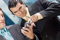 Close-up of two businessmen using a palmtop