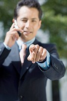 Portrait of a businessman talking on a mobile phone and pointing forward