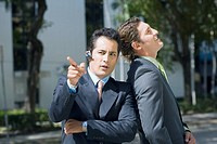 Businessman leaning against another businessman and pointing forward