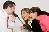 Side profile of a businessman talking on the telephone with two businesswomen looking at him and smiling