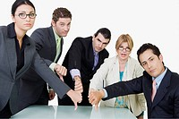 Portrait of two businesswomen and three businessmen showing thumbs down sign