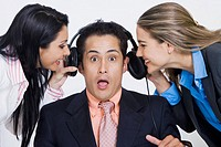 Close-up of two businesswomen pulling headphones of a businessman