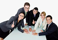 Portrait of two businesswomen and three businessmen placing their hands on the table
