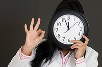 Close-up of a businesswoman holding a clock in front of her face and making an OK sign