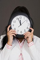 Close-up of a businesswoman holding a clock in front of her face