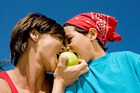 Low angle view of a mid adult woman biting an apple with her son