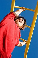 Low angle view of a mid adult man hanging on monkey bars