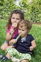 Two sisters sitting in a park and eating candies