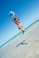 Low angle view of a mid adult woman playing with a beach ball on the beach