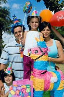 Mid adult couple with their daughters celebrating a birthday party
