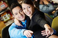 Close-up of a mid adult man with his arm around a teenage girl in a casino and pointing forward