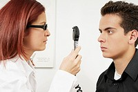 Close-up of a female optometrist examining eyes of a young man