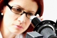 Close-up of a female optometrist using a phoropter