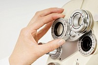 Close-up of an optometrist´s hand adjusting a phoropter
