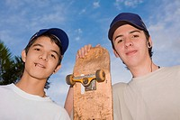 Portrait of two young men standing with a skateboard