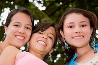 Portrait of a teenage girl smiling with two young women