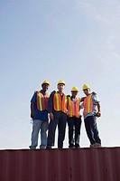Portrait of workers standing on cargo container