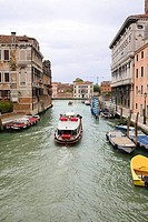 Boats and a water taxi in a canal, Venice, Italy