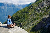 Woman sitting on a rock. Hordaland. Norway