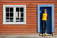 Woman standing in front of a wooden house