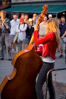 Young woman playing double bass in a centric street. Oslo. Norway