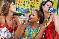 Three young women drinking water from bottles