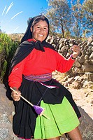 Portrait of a young woman spinning a reel of thread, Taquile Island, Lake Titicaca, Puno, Peru