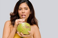 Portrait of a young woman drinking coconut milk