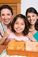 Portrait of a mid adult woman and her two daughters smiling with a tray of breads in the kitchen