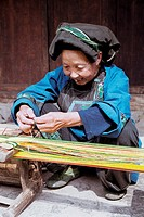 Cheerful Miao minority older woman making a brocade in Miao minority housing of Dehang, Jishou City, Xiangxi Prefecture, Hunan Province, People's Repu...