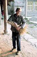 View of a cheerful mature man making broom, Taishun County, Zhejiang Province, People's Republic of China, FOR EDITORIAL USE ONLY