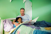 Father with daughter reading book in bedroom