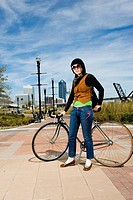 Portrait of a young woman standing with her bicycle