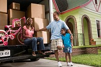 Portrait of a family standing outside a house by moving truck