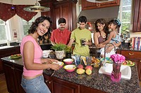 Family in the kitchen with mother preparing food