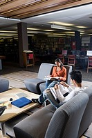 Students in library sitting on chairs studying