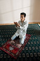 A Muslim man praying on a prayer mat