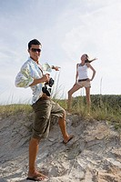 Young man pointing at a young woman at the beach
