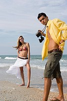 Young man photographing scantily clad woman on the beach